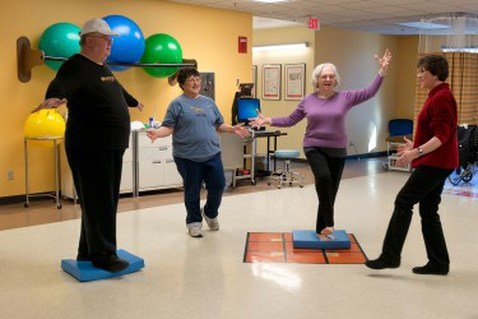 Photo Description: Four older adults doing balance exercises.